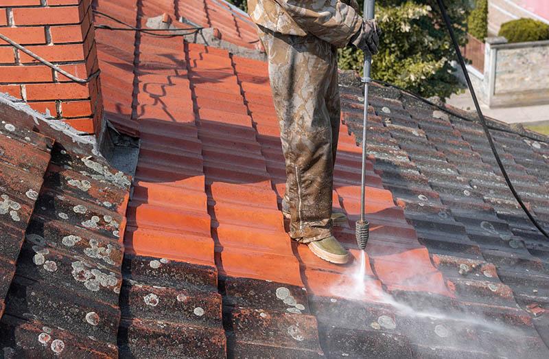 Mitarbeiter entfernt Grauschleier und Verschmutzung von Dach